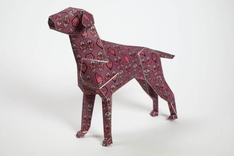 A dark pink paper dog model in 3D form. Part of an international design exhibition hosted by Lazerian where artists and designers were invited to customise the paper form in their own individual styles. This dog was designed by Gary Milne. It has symbols on its body that represent faith and mortality.