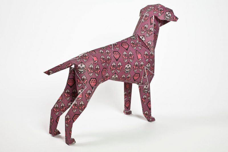 Back view of a dark pink coloured paper dog sculpture. The design on the dog has symbols on it that represent faith, commodity and mortality and was designed by artist Gary Milne. Part of a exhibition by design studio lazerian.