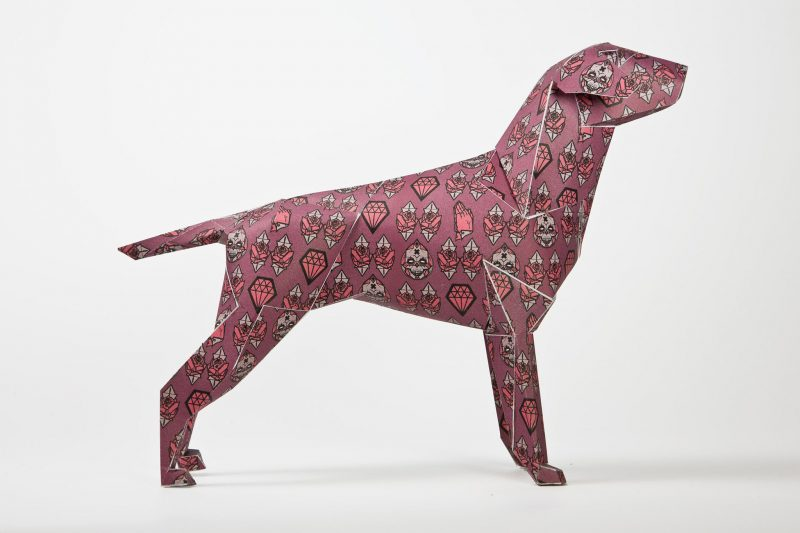 Side view of a pink paper dog model with symbols over its body to represent faith, commodity and mortality. The artist Gary Milne was part of an internationally renowned exhibition by design leaders Lazerian where they invited 101 designers and artists to customise the Lazerian mascot- a dog called Gerald.