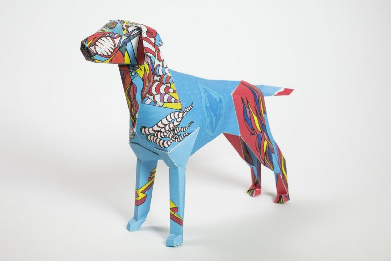 A colourful paper dog designed sculpture in a 3D form. Part of an international exhibition by design studio Lazerian whereas they invited 101 artists and designers from around the world to customise the Lazerian mascot who is Gerald the Lazerian dog. This design is from Goo for Brothers and is reminiscent of childhood memories. The dog had a bright blue centre with its head and back legs in a firer like style with flames in red, yellow and blue.