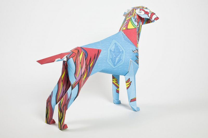 Back view of a paper dog model in a sculptural 3D form. The dog has been designed with a bright blue centre and either side of that on its head and back legs is a fire style whereas it looks like flames but in red, yellow and blue. Designed by Goo For Brother it was inspired by childhood memories. Part of an inernational exhibition from design studio Lazerian