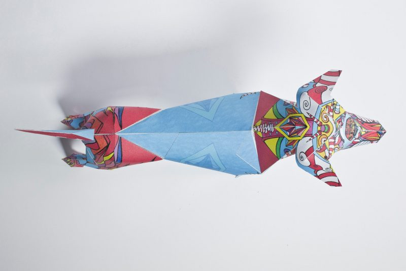 Overhead view of a paper dog model. Designed by Goo for Brothers in a style that evokes their childhood memories. Part of a design exhibition from Lazerian. The dog is very colourful with a bright blue centre. On either side- its head and back legs it has the style of flames alight but they are red, blue and yellow.