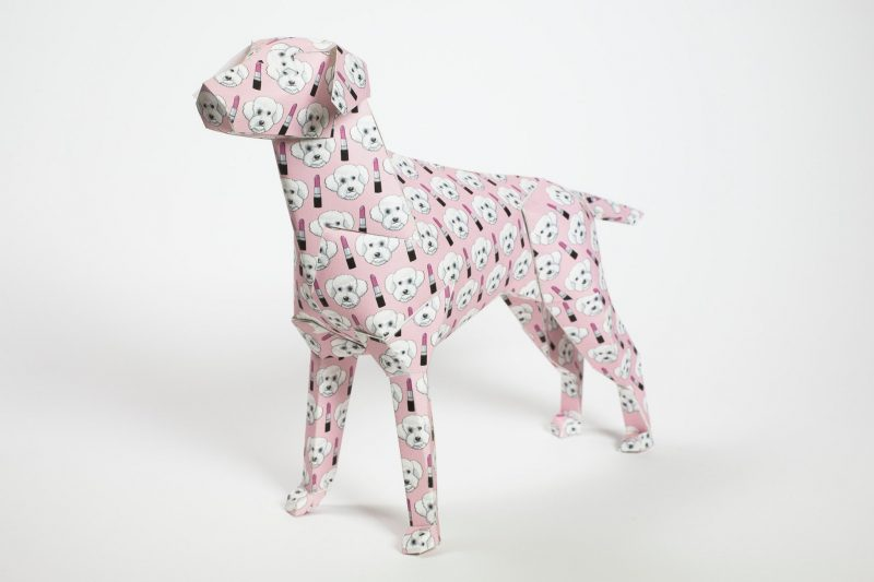A baby pink paper dog design in 3D sculptural form. Part of an exhibition from Lazerian where artist and designers were invited to customise the paper dog form in their own unique style. This version is a baby pink dog with alternating lipsticks and a cute doggie face. The inspiration for the dog is from the artist own. Designed by Grande Dame