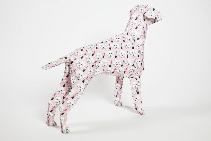 Back view of a baby pink paper dog. A 3D form sculpture this dog is covered in images of lipstick and a cute dog face. Designed by Grande Dame for a international design exhibition by Lazerian