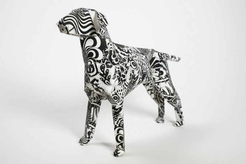 A black and white pattern inspired by the swinging 60's on a paper dog sculpture 3D model. part of an international exhibition by design studio Lazerian who invited artists and designers to customise the Lazerian mascot which is a dog, and create their own original design on the 3D model. This particular design is by artist and well know designer and creator Grande Dame.