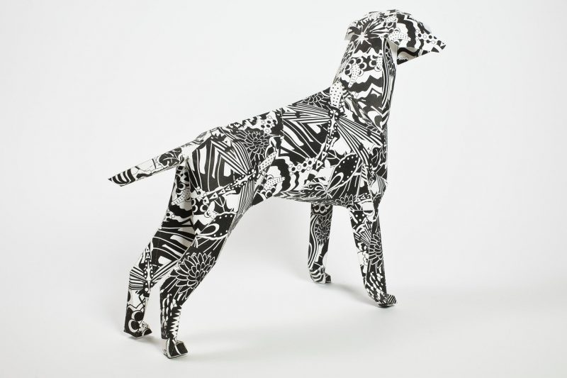 A back view of a paper dog model in a 3D sculptural form. The dog has a black and white design inspired by the swinging 60's and designed by artist Grande Dame. It is aort of a design exhibition by Lazerian who invited artist and designers to create their own signature design on the paper dog model which is also the Lazerian mascot.