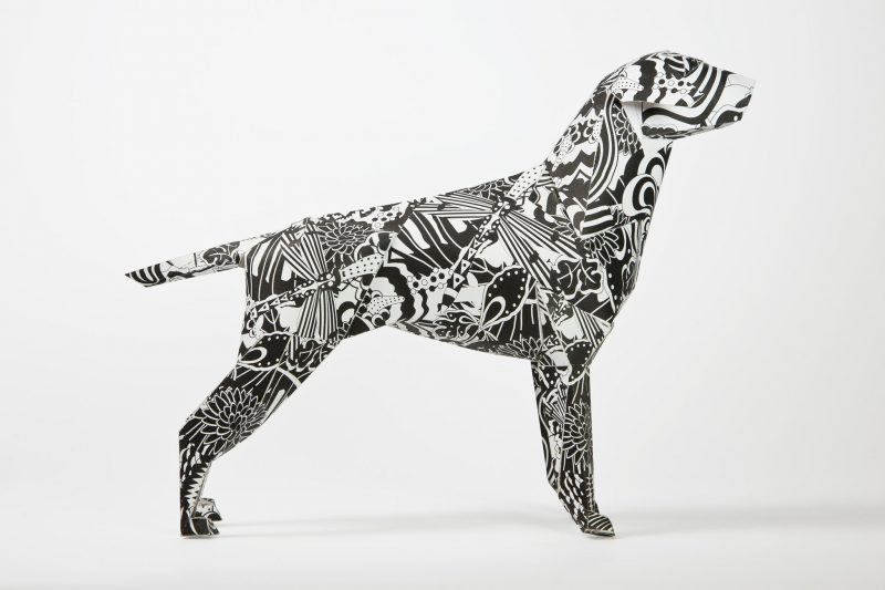 Side view of a paper dog model in 3D form. the dog is a blac and white pattern inspired by the swinging 60's. Designed by leading artist Grande Dame and part of an international design exhibition from designers and creators lazerian.