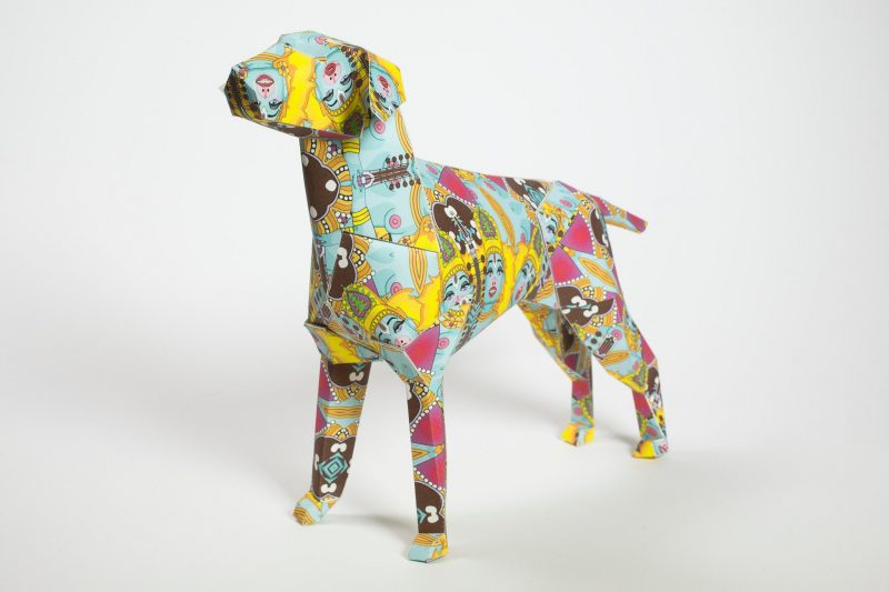 A colourful paper dog model with a design that is inspired by Hindu gods in particular Kushi the goddess monkey dog of happy living. The 3D sculptural model is very colourful in a Hindu style with yellows, pinks and blues all over and with faces of the female gods. Designed by artist Grande dame it is also part of a design exhibition from Lazerian.