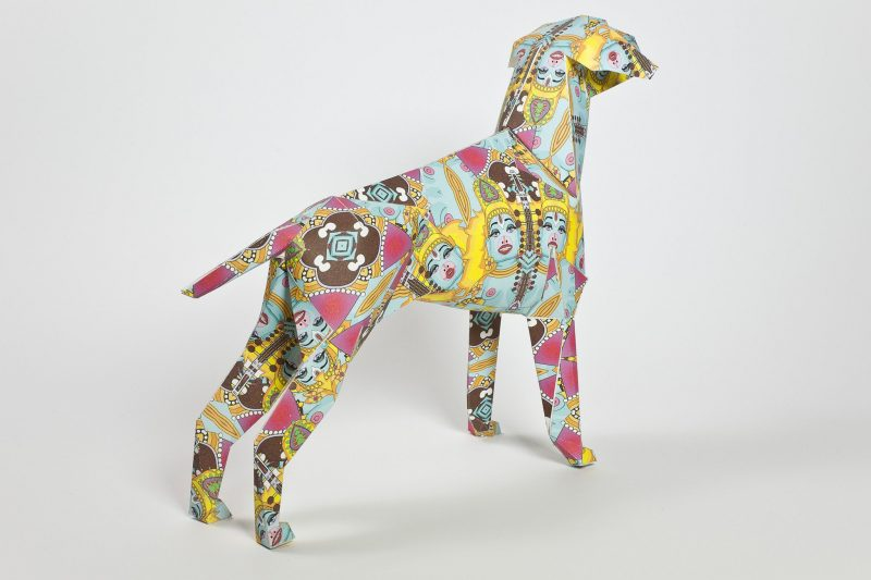 A paper dog model in a 3D sculptural form which is the mascot from leading design studio Lazerian. Part of an international exhibition where artists and designers customise the dogs in their own styles. this one is by artist Grande Dame. She has given it a Hindu style with a colourful vibe including pinks, yellow and light blue. The dog has severa female god faces all over it.