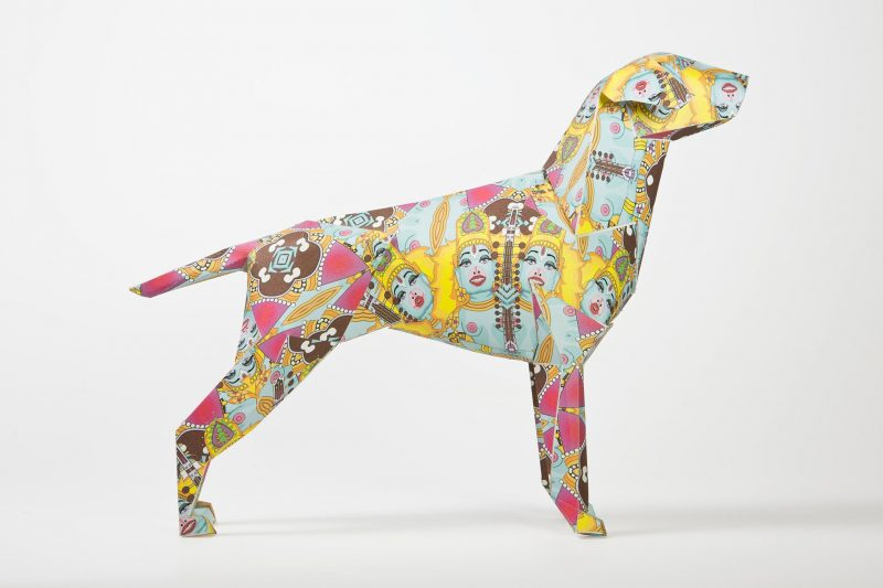 Side view of a paper dog sculpture in 3D form with a colourful Hindu inspired pattern acro. It also has female Hindu god faces on it. Designed by leading artist Grande Dame as part of an international exhibition by designers and creators Lazerian. The paper dog is lazerians mascot and Lazerian invited artist and designers to customise the paper dog model in their own signature styles