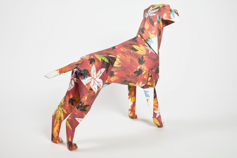 A back view of an autumnal designed paper dog model. The dog has a design on it that looks like it is covered in autumn leaves. Autumnal colours such as golden brown, oranges, browns and reds- with occasional yellows are all featured. Designed by leading artist and illustrator Guy McKinley. Part of an exhibition by design studio Lazerian who invited artists and designers to add their own designs onto the paper dog sculptures.