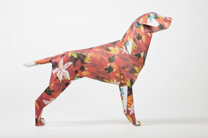 Side view of an autumnal looking paper dog sculpture. The model which is in 3D form is covered with autumn coloured leaves such as reds, yellows and golden browns. Created for an exhibition whereas 101 different artists and illustrators were asked to customise the dog in their own signature styles. This design is by artist and illustrator Guy McKinley.