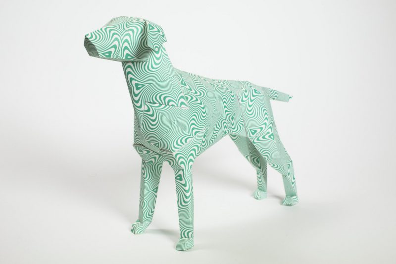 A psychedelic green pattern on a paper dog sculpture. Part of an exhibition from design studio lazerian. The paper dog is the studios mascot and they invited several artists and designers to customise the paper dog sculptures in their own designs. This design is from Hawaii design.