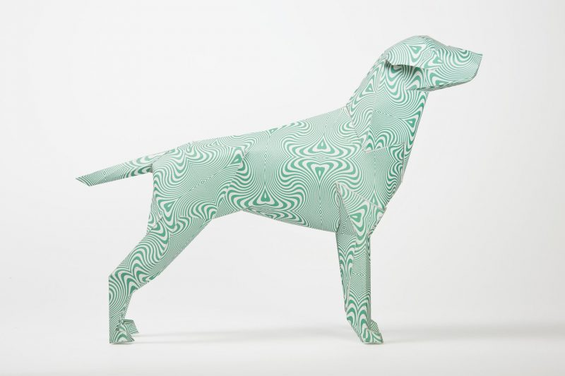 Side view of a paper dog sculpture that has a green lined psychedelic style pattern all over it. Part of an inernational exhibition by design leaders Lazerian. They allowed several artists and designers to create their own signature designs and styles onto the paper dog which is also the Lazerian mascot. This design is from leading design group Hawaii Design