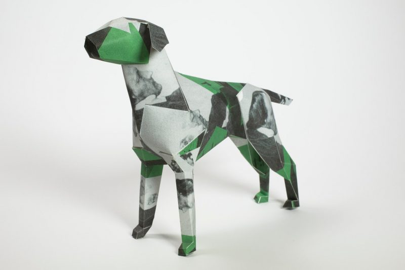 A green, black and light grey patterned paper dog model in a 3D sculptural form. It also has balck and white photos of mens faces on it. Part of an exhibition by leading designers Lazerian. the dog is the companies mascot and they invited artists and designers to come and design something unique to be placed onto the paper dog.