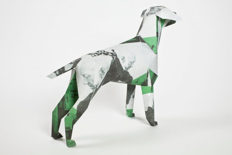 A back view of a paper dog model with a green, grey and balck design over it. Designed by designers Hidden Leisure it also sports a collage effect of faces of old men in a black and white form. Part of an exhibition by designers Lazerian. Artist and designers were invited to customise the paper dog sculptures in their own signature styles.