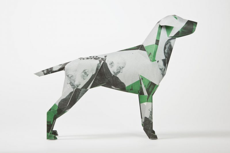 Side e view of a paper dog model that has green, grey and black and white patches of colour. It also has black and white cutout photos of old men. This design is part of a international project and exhibition by design leaders Lazerian. 101 artist, designers and creators were all invited to customise the dog in their own styles.