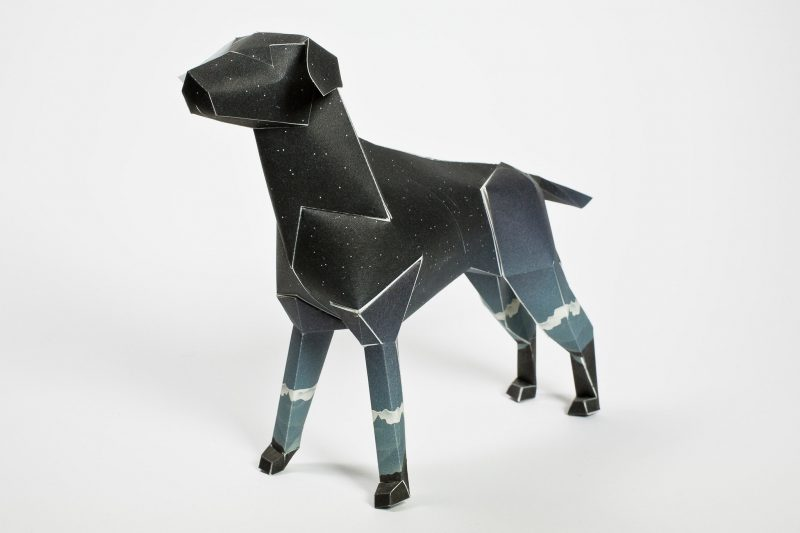 Paper dog sculpture in 3D form. Very dark in colour with white mountain tops around the middle of its legs. Part of an exhibition by leading designers Lazerian. The paper dog is Lazerians mascot and the project was to invites artists and designers to showcase their designers onto the body of the paper dog sculpture.This design is by illustrator and designer Jack Hughes