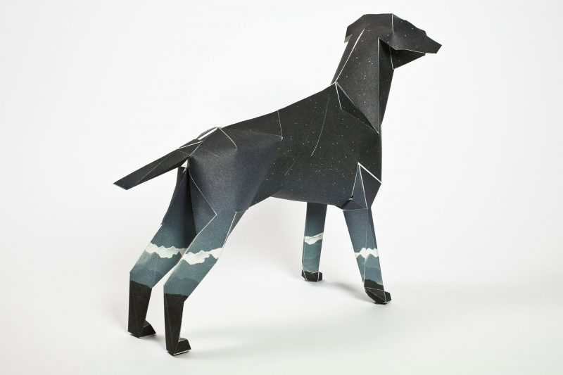 A back view of a dark paper dog in a 3D sculpture form. The dog has white mountain tops on the middle of each of its four legs. Part of a worldwide exhibition and project by Lazerian. The project was to get artists, designers, illustrators and creators to design a coat for the paper dog who is also Lazerians mascot. This coat was designed by Jack Hughes.