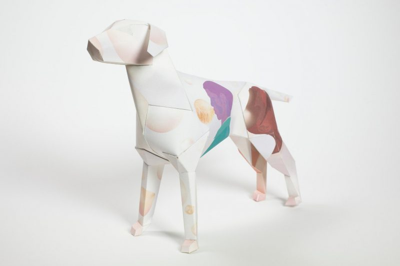 A paper dog sculpture that is the mascot of design company Lazerian. The studio decided to invite designers and artists to add their contemporary and unique styles onto the paper dog sculpture. This design is by illustrator and designer James O'Connell. The front half of the dog is white , the middle has a silhouette of a woman blowing bubblegum. The silhouette is in a blue and purple colour. The back end of the dog is a silhouette of a man whose face is green and hat is a light orange