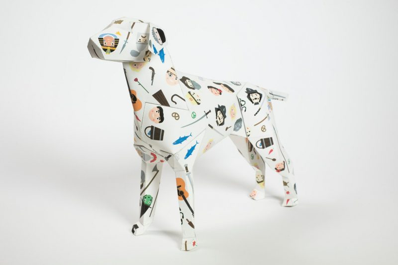 A paper dog design in a 3D sculpture form. The mascot of design studio Lazerian, they organised a exhibition to invites designers, artists and illustrators to customise the paper dog sculpture. This dog is white in background with small characters such as Egyptians, Indians, cowboys etc. The design is from children's illustrator Jamie Malone