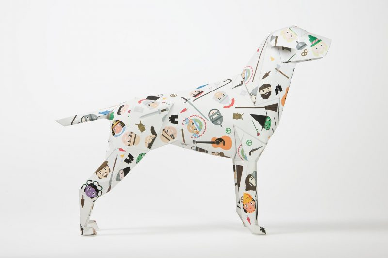 Side view of a paper dog sculpture with images all over it. It has faces of child like illustrations of cowboys and Indians, Egyptians and soldiers dotted all over it. Part of an exhibition by design studio Lazerian, whereas they asked artists, designers and illustrators to customise the dogs in their own signature styles. This design is from children's illustrator Jamie Malone.
