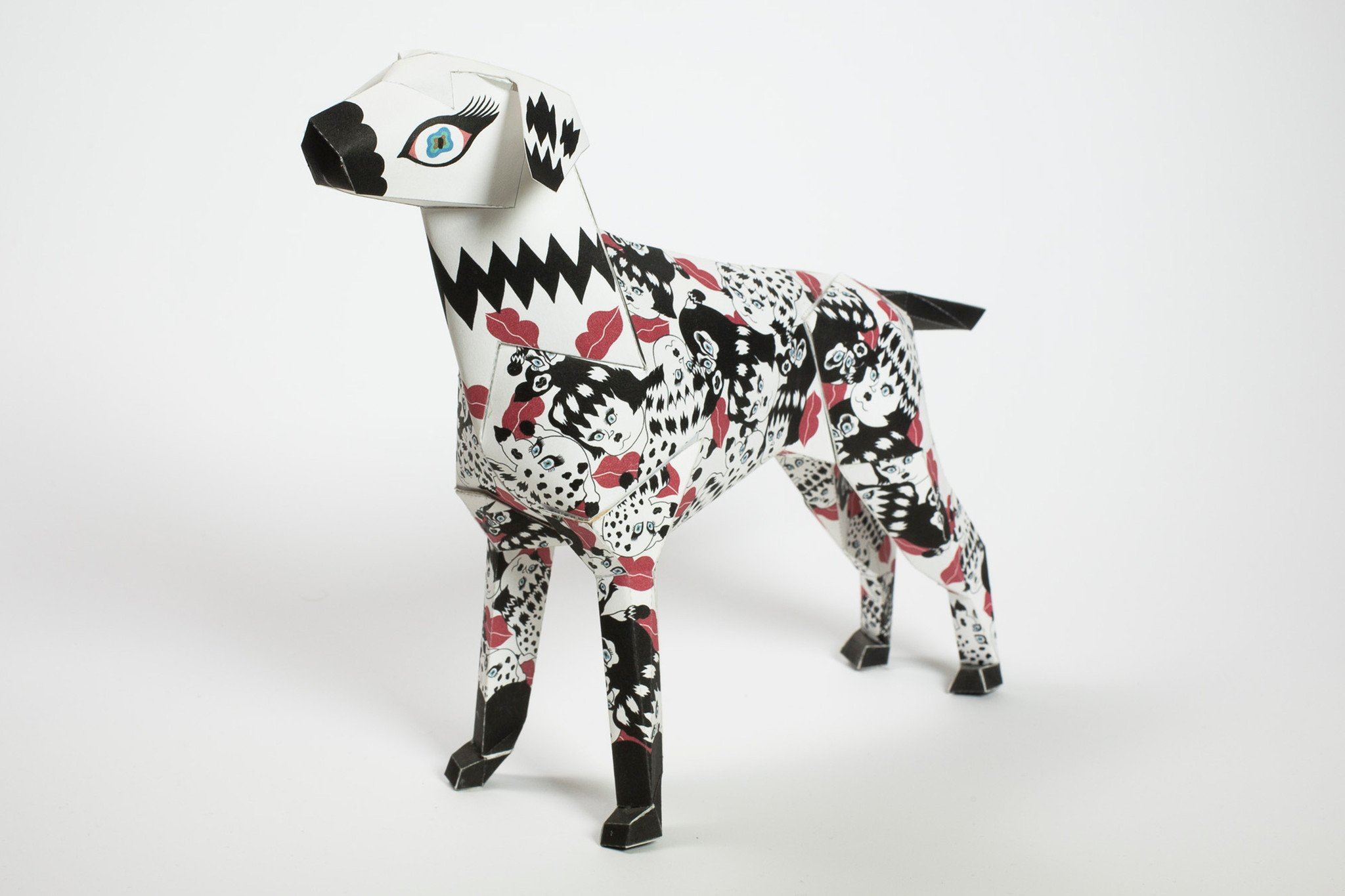 This paper dog sculpture is in 3D form and has a black and white pattern all over it with red lipstick marks spread sporadically around its body. Designed by artist Jang Koal as part of an international design exhibition by British design studio Lazerian. The paper dog is Lazerians mascot and was th emain focus in this project. Artist and designers from around the world were all invited to put their own spin and design onto the paper dog sculpture