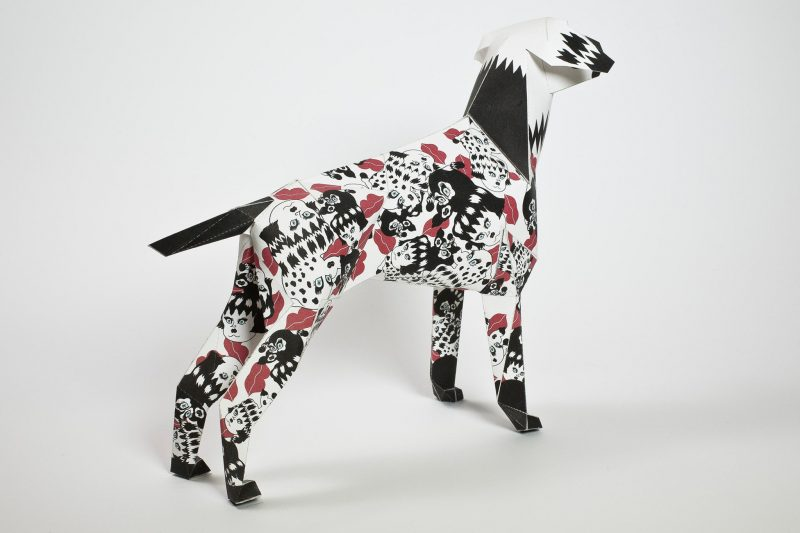 A paper dog model sculpture facing with it back to the front of the screen. It is a black and white designed pattern on its coat with lots of red lipstick marks around its body. designed by illustrator and creative Jang Koal with the markings being lucky charms for the dog also known as Gerald. Gerald is the mascot of internationally renowned design and creative studio Lazerian. Lazerian set up a project that toured as a worldwide exhibition to customise the dog in their own signature styles.
