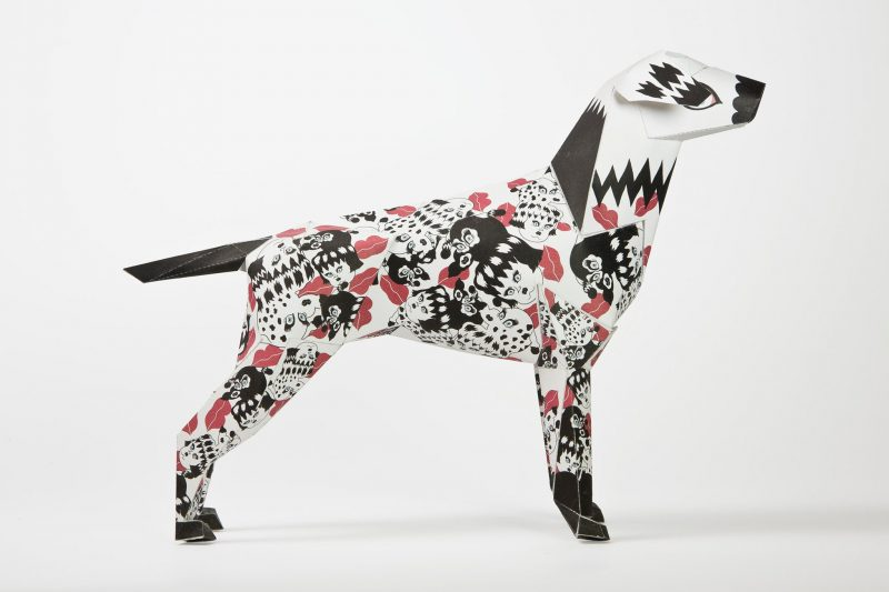 A side view of a black and white pattern paper dog sculpture. The paper model also has several red lipstick marks all over it. Designed by Jang Koal as part of a project by Lazerian. The paper dog is the mascot of LAzerian. the project was also an exhibition whereas artist, creatives and designers were invited to put their own stamp and designs onto the paper dog model.