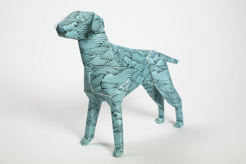 A paper dog model in 3D form with a blue wave repeat pattern on it. Designed by Joe Wilson and part of an exhibition by design studio Lazerian. the dog is the mascot of Lazerian.