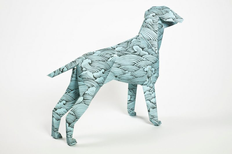 A blue repeat pattern of waves on a paper dog sculpture by artist and designer Joe Wilson. Part of a Lazerian exhibition whereas artist and designers were invited to design their own dog pattern or images in their own signature styles.