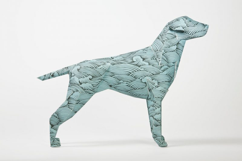 Side view of a paper dog model in 3D form. The pattern is a repeated wave style in blue which is the signature style of artist Joe Wilson. PArt of an exhibition by Lazerian