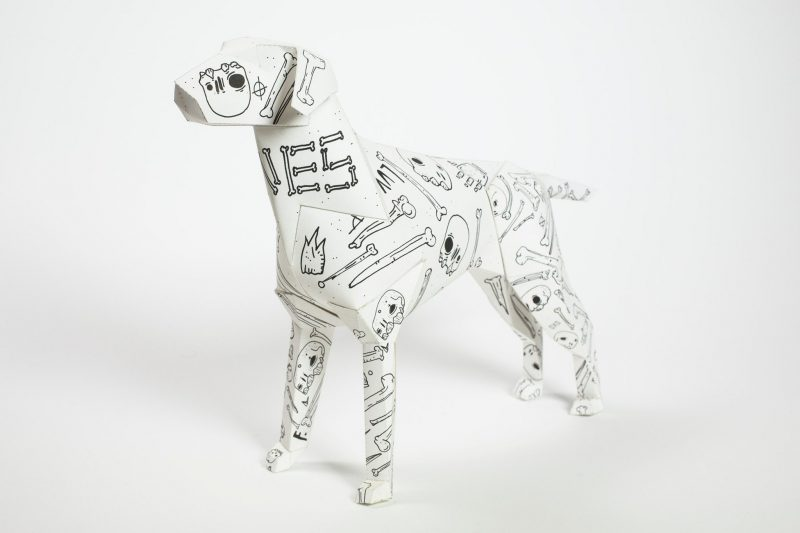 A paper dog sculpture in 3D form with line drawings on the white body. the black lined drawing are bones, skulls and the word BONES spelt out on the dogs neck. Design by artist Mr. Millerchip. Part of an international exhibition and project by design studio Lazerian. the dog is Lazerians studio mascot. the exhibition consisted of 101 designers and artists all contributing to designing an individual dog sculpture in their own signature styles.