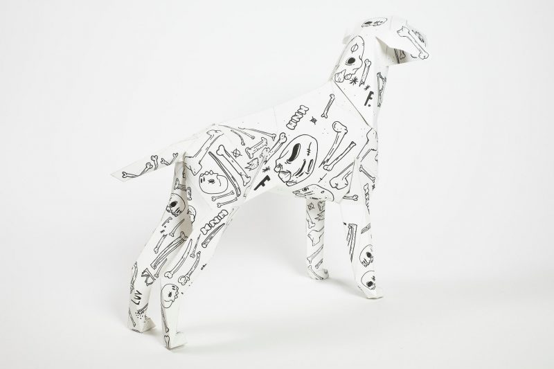 Back view of a paper dog model in 3D form. The dog has a white background with line drawings in black of bones and skulls. Part of an exhibition by design studio Lazerian. The dog is a mascot of the design studio. designers and artists were asked to put their own signature styles onto the dog model.
