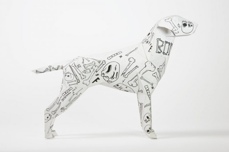 Side view of a paper dog sculpture. The white dog is a mascot of design studio Lazerian who also held an exhibition for artist and designers to put their own designs onto the paper dog. This dog is white with black line drawings of skulls and bones by artist Mr. Millerchip