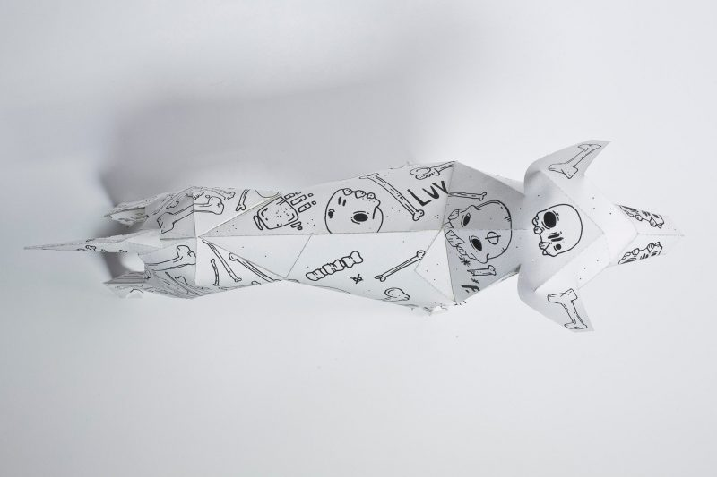 Over head view of a white paper dog sculpture. It has black lined drawings of skulls and bones. Designed by Mr. millerchip for an international exhibition where designers and artist were asked to put their own signature designs onto the paper dog who is a mascot of design studio Lazerian