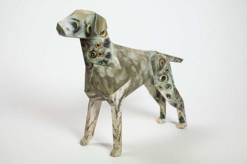 left hand view of a paper dog model in 3D form. The dog is part of an exhibition by design leaders Lazerian. The paper sculpture is a mascot of Lazerian. The design on the paper dog is by John Pusateri and has a selection of bird eyes possible owls on its back legs and its neck and mouth area.