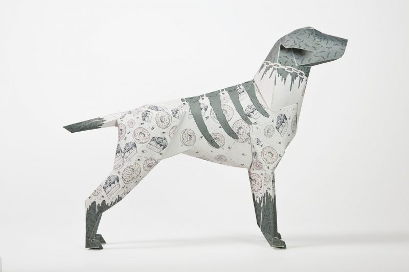 A paper dog model in 3D sculptural form. designed for an international exhibition by design leaders Lazerian. The dog is symbolic as it is Lazerians studio mascot. The exhibition invited artist, designers and other creatives to put their own designs onto the paper sculpture to show off their signature styles. This version has been designed by leading international artist Josan Gonzalez. The dog has a grey head and tail and also 4 grey paws that rise slightly to resemble socks. There are also 4 lines on the top of the body that resemble ribs.