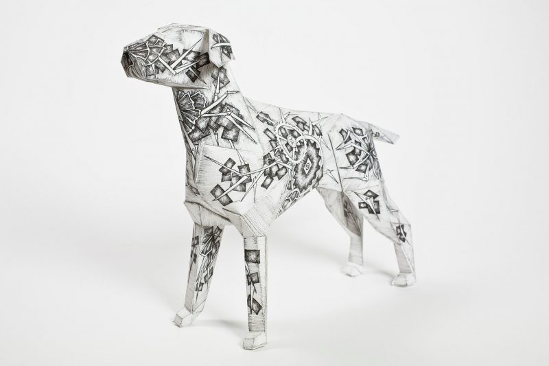 A dark grey and white paper dog sculpture that has old fashioned clock wheels, cogs and pireces all over it. As part of an international exhibition from design leaders Lazerian. The paper dog is the studios mascot and in honour of this they invited artist and designers to contribute their designs to the body of the paper sculpture. This design is by international artist and designer Juli Jah