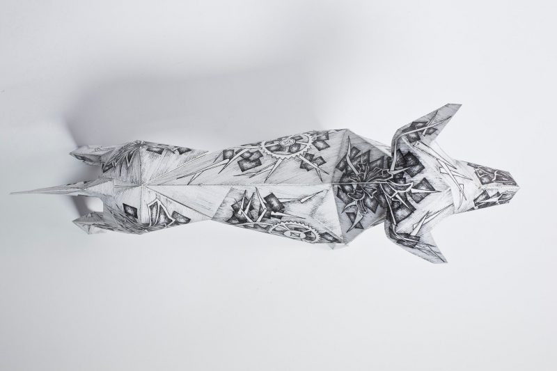 Over head view of a paper dog model in a 3D sculptural form. The design on the dog is from Juli Jah and features several clock pieces drawn all over its body. The pieces are vintage looking and are cogs and wheels. in grey on a white background. As part of a exhibition by design studio Lazerian as part of an international exhibition whereas artists and designers customise the dogs in their own signature styles.
