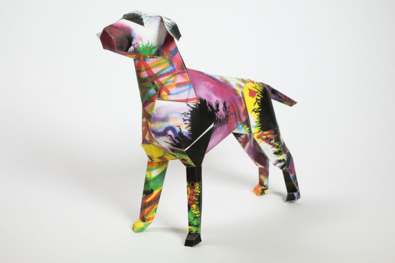 Paper dog sculpture with purple, yellow, greens and blue all over it like sploshes all over it. Designed by artist and illustrators Kerry Roper. As part of an exhibition from Lazerian who invited designers and artists to customise the paper dogs in their own signature styles.