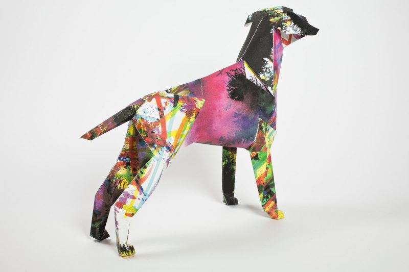 Back view of a paper dog sculpture in 3D form. As part of an exhibition by Lazerian who invited artists and designers to customise the paper dog models. This design is sploshes of colours including purples, yellows, oranges and yellows and pinks by illustrator Kerry Roper.
