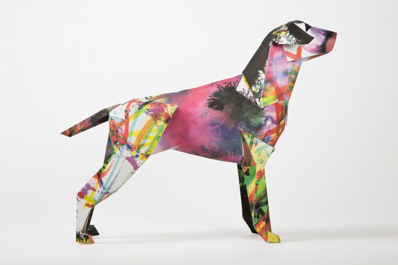 Side view of a paper dog sculpture with design from illustrator Kerry Roper. The design featured yellow, purple, green and pink sploshes all over the body. Part of an interantional design exhibitio by studio Lazerian. The paper dog is Lazerians studio design mascot and an exhibition was formed by invited several artists, illustrators, designers and creatives to customise the paper dog sculptures using their own designs.
