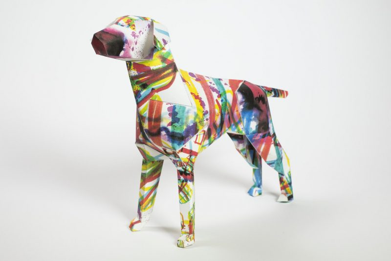 A paper dog sculpture from an exhibition from design studio Lazerian. Lazerian have a mascot that is the paper dog and wanted artists and designers to customise the paper model by using their own skills and designs. This dog is from illustrator Kerry Roper and has splashes of colour sporadically on the dog strcuture. Colours include pink, purple, yellow and greens.