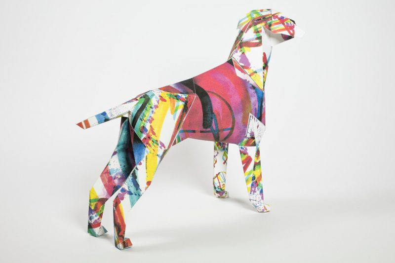 Back view of a paper dog model by illustrator Kerry Roper. It is part of a design exhibition by Lazerian who used their studio mascot, the dog, to make into a paper dog sculpture. They then asked artist and designers to create their own designs and ideas onto the dog as part of the exhibition