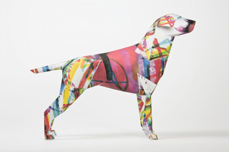 A paper dog sculpture which is the mascot of design studio Lazerian. Part of an exhibition whereas Lazerian asked illustrators, artists and designers to all add their own designs to the paper dog model. This design is from renowned and respected illustrator and designer Kerry Roper. The deisng is abstract with splashes of colours all over the dog. Colours such as pinks, purples, yellows and blues are seen.