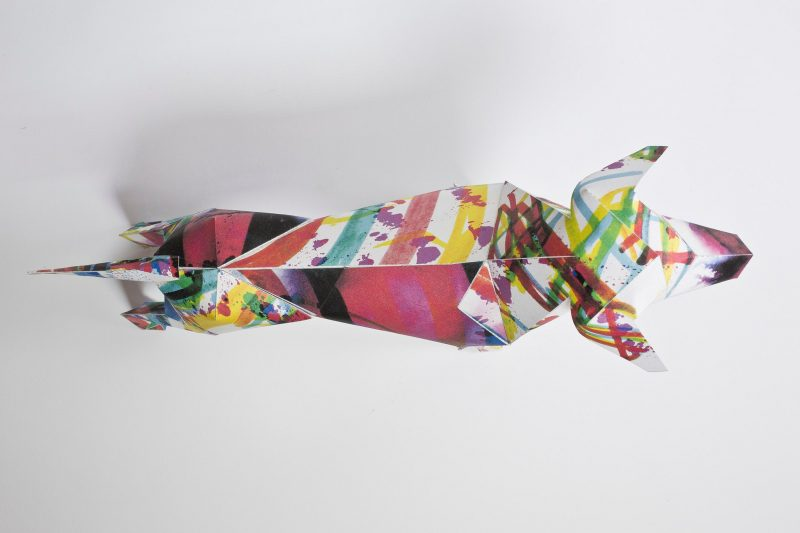 Over head view of a paper dog model in 3D form. Part of a design exhibition by design leaders Lazerian. Lazerian used their studio mascot and put it into paper 3D form and asked designers and artist to customise the body of the model. This dog has been customised by illustrator Kerry Roper. He has added splashes of colour all over the dog using purples, yellows, pinks and greens.