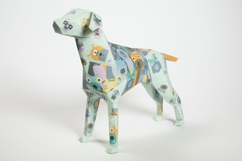 A light green coloured paper dog sculpture in 3D form covered with childfriendly illustrations of puppy dog faces in yellows and greys. DEsigned by illustrator and artist Kev Munday. He found indpiration for the design from memories of walking her own dog as a child. Part of a design exhibition where as design leaders, who designed and made the paper dogs as the mascot of their studio, invited artist and designers to put their own stamp on the paper models.