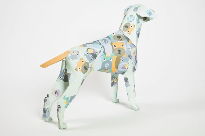 Back view of a paper dog model in a 3D sculptural form. As part of an exhibition where artist and designers were invited to customise the paper dog models in using their own styles. This design from Kev Munday is covered in cartoon/child like friendly illustrations of dogs faces in grey and yellows.