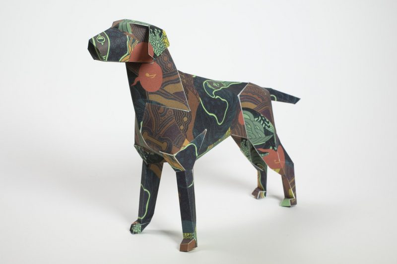 A dark coloured paper dog sculpture with 3D form. As part of an exhibition from design studio Lazerian whereas they asked designers and artists to customise the paper dog model that is also their studio mascot. This dog is by Kristina Collantes and is inspired by sea foilage. It has dark pattern such as circles and lines in colours like dark green, brown and dark brown.